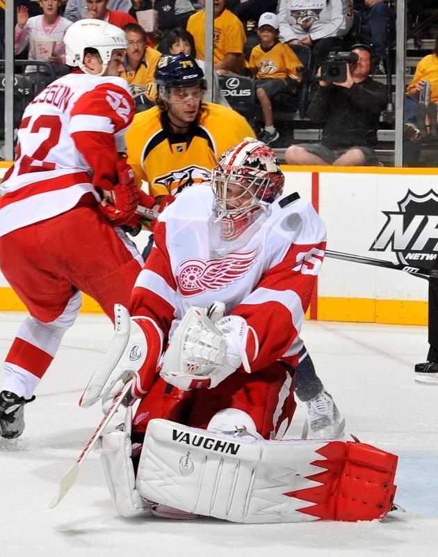 NASHVILLE, TN - APRIL 20: Goalie Jimmy Howard #35 of the Detroit Red Wings takes a puck off the shoulder in Game Five of the Western Conference Quarterfinals against the Nashville Predators during the 2012 NHL Stanley Cup Playoffs at the Bridgestone Arena on April 20, 2012 in Nashville, Tennessee. (Photo by Frederick Breedon/Getty Images)