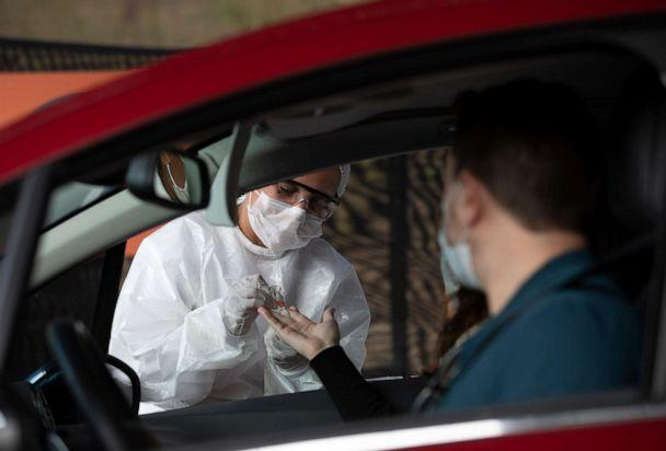 PHOTO: A health worker collects a sample from a person at a drive-thru testing site for COVID-19 in Niteroi, Brazil, on June 3, 2020, amid the coronavirus pandemic. (Silvia Izquierdo/AP)