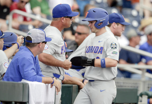 Florida's Deacon Liput, right, bumps fists with Florida coach Kevin O'Sullivan after he scored a run against Texas on a single by Jonathan India in the first inning of an NCAA College World Series baseball elimination game in Omaha, Neb., Tuesday, June 19, 2018. (AP Photo/Nati Harnik)