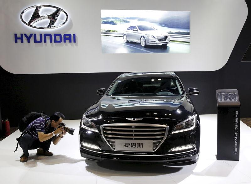 File photo of a visitor taking picture of Hyundai Genesis model during the Imported Auto Expo in Beijing