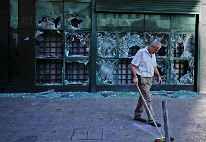 A man cleans up outside a bank that was vandalised by protesters in Lebanon's northern city of Tripoli (AFP Photo/Ibrahim CHALHOUB)