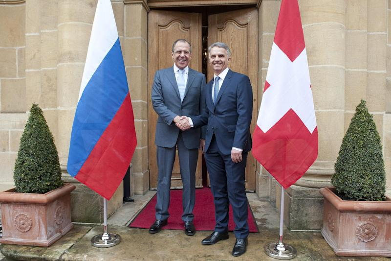 Russian Foreign Minister Sergei Lavrov, left, shakes hands with Switzerland's Federal Councillor and Foreign Minister Didier Burkhalter, right, during a working visit in Neuchatel, Switzerland, Friday, April 12, 2013. (AP Photo/Keystone/Sandro Campardo)