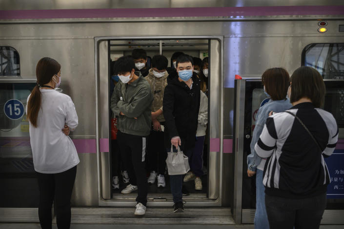 Commuters wear protective masks as they exit the subway during rush hour on Wednesday in Beijing. China lifted its lockdown on the city of Wuhan, the first epicenter of COVID-19 after 76 days last week, allowing healthy people to leave. (Kevin Frayer/Getty Images)