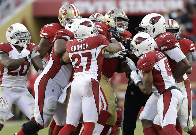 San Francisco 49ers offensive guard Laken Tomlinson, center, shoves Arizona Cardinals players during the second half on Sunday. (AP)
