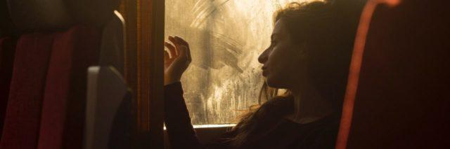 photo of bored tired looking woman on train or bus looking out of dirty window