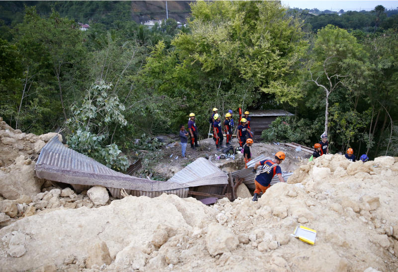 Rescuers dig through the rubble to search for possible survivors, with some sending cellphone text messages pleading for help, following a landslide that buried dozens of homes in Naga city, Cebu province central Philippines on Thursday Sept. 20, 2018. A landslide set off by heavy rains buried homes under part of a mountainside in the central Philippines on Thursday, and several people are feared buried, including two who sent text messages seeking help. (AP Photo/Bullit Marquez)