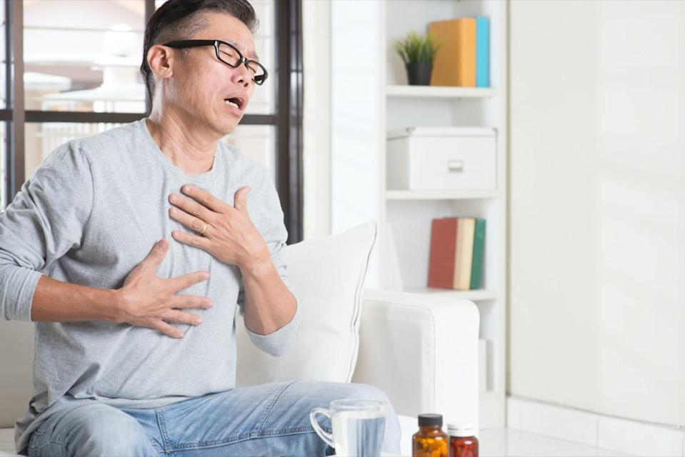 Portrait of casual 50s mature Asian man heartburn, pressing on chest with painful expression, sitting on sofa at home, medicines and water on table.