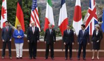 FILE - In this Friday, May 26, 2017 file photo, leaders of the G7, from left, Canadian Prime Minister Justin Trudeau, German Chancellor Angela Merkel, U.S. President Donald Trump, Italian Prime Minister Paolo Gentiloni, French President Emmanuel Macron, Japan's Prime Minister Shinzo Abe, and British Prime Minister Theresa May pose during a group photo for the G7 summit in the Ancient Theatre of Taormina in the Sicilian citadel of Taormina, Italy. Millions of women admire the 67-year-old for breaking through the glass ceiling of male dominance in politics, and she's been lauded as an impressive role model for girls both at home and around the globe. (AP Photo/Andrew Medichini, File)