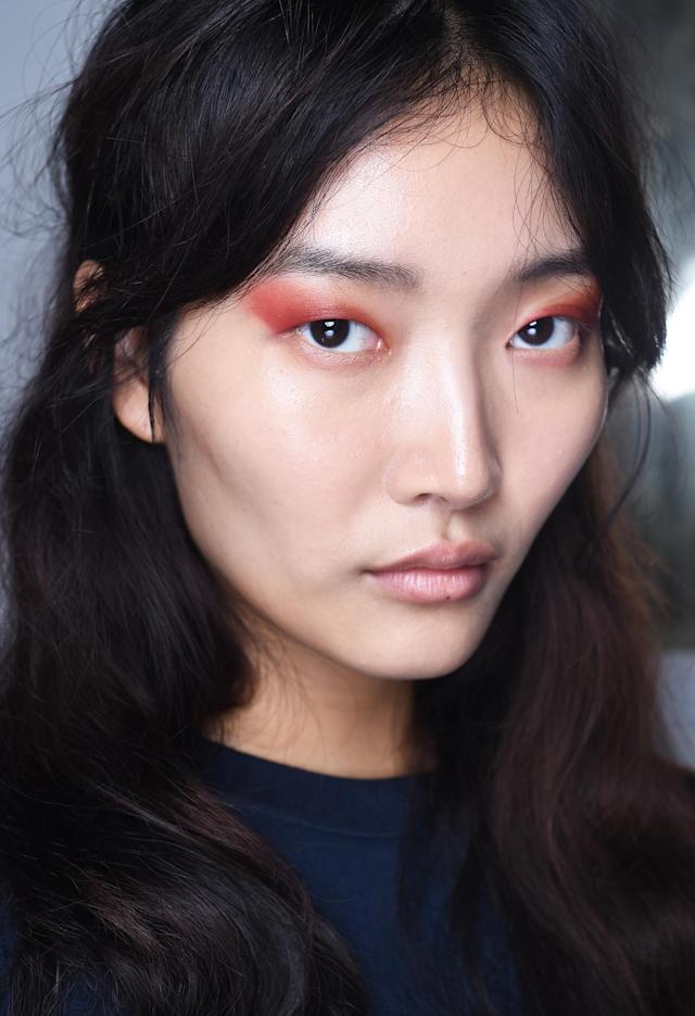 <p>Bold orange eyeshadow accentuates this model's brunette locks. (Photo: NARS) </p>