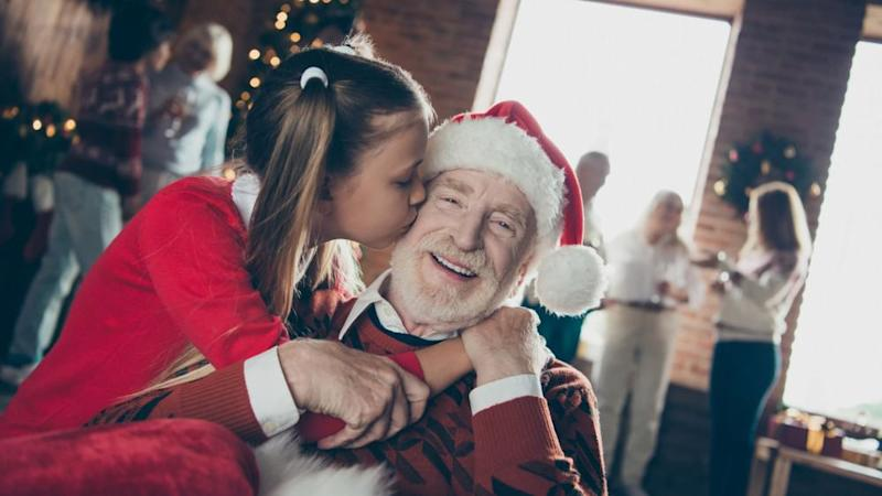Little girl kissing her granddad at christmastime