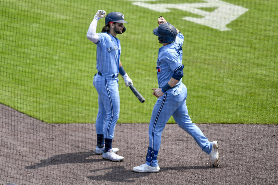 Toronto Blue Jays' Danny Jansen, right, is congratulated by teammate Bo Bichette after hitting a solo home run against the Texas Rangers during the fifth inning of the first baseball game of a doubleheader in Buffalo, N.Y., Sunday, July 18, 2021. (AP Photo/Adrian Kraus)