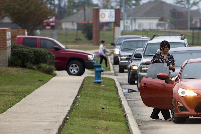 Cars line up to pick up students outside of North Shore High School after a shooting occurred Wednesday, Dec. 5, 2012, in Houston. Police say a high school student shot himself while in the back of a patrol car after being arrested earlier on suspicion of taking a gun to campus. (AP Photo/Houston Chronicle, Cody Duty)
