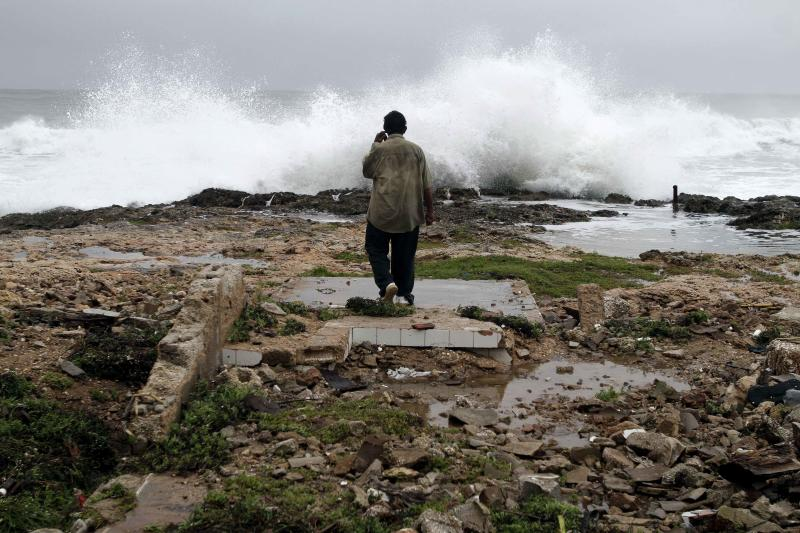 A man walks among the ruins of a home destroyed by Hurricane Sandy in Gibara, Cuba, Thursday, Oct. 25, 2012. Hurricane Sandy blasted across eastern Cuba on Thursday as a potent Category 2 storm and headed for the Bahamas after causing at least two deaths in the Caribbean. (AP Photo/Franklin Reyes)