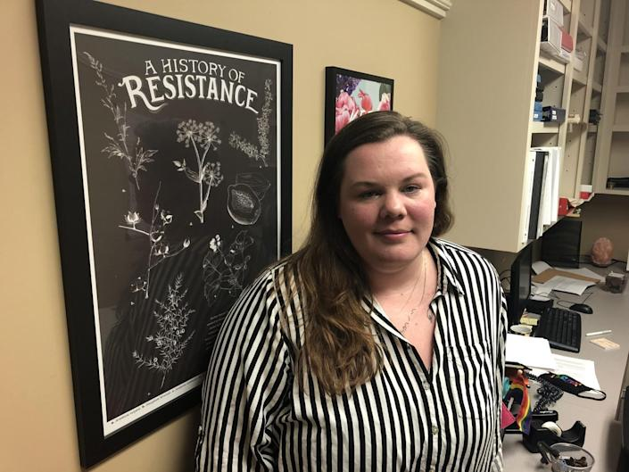 """Ashley Brink with a wall poster that reads """"A History of Resistance"""""""