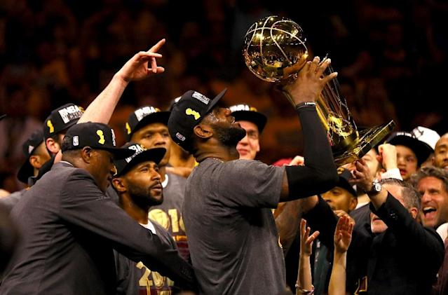 LeBron James of the Cleveland Cavaliers holds the Larry O'Brien Championship Trophy after the Cavs beat the Golden State Warriors 93-89 in Game 7 of the 2016 NBA Finals in Oakland, California, on June 19 2016 (AFP Photo/Ezra Shaw)