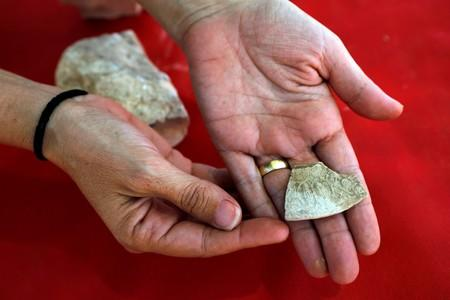 An archaeologist from the Israel Antiquities Authority shows off one of the findings discovered at the site where the remains of a mosque was uncovered and which the authority say is one of the world's oldest mosques, in the outskirts of Rahat