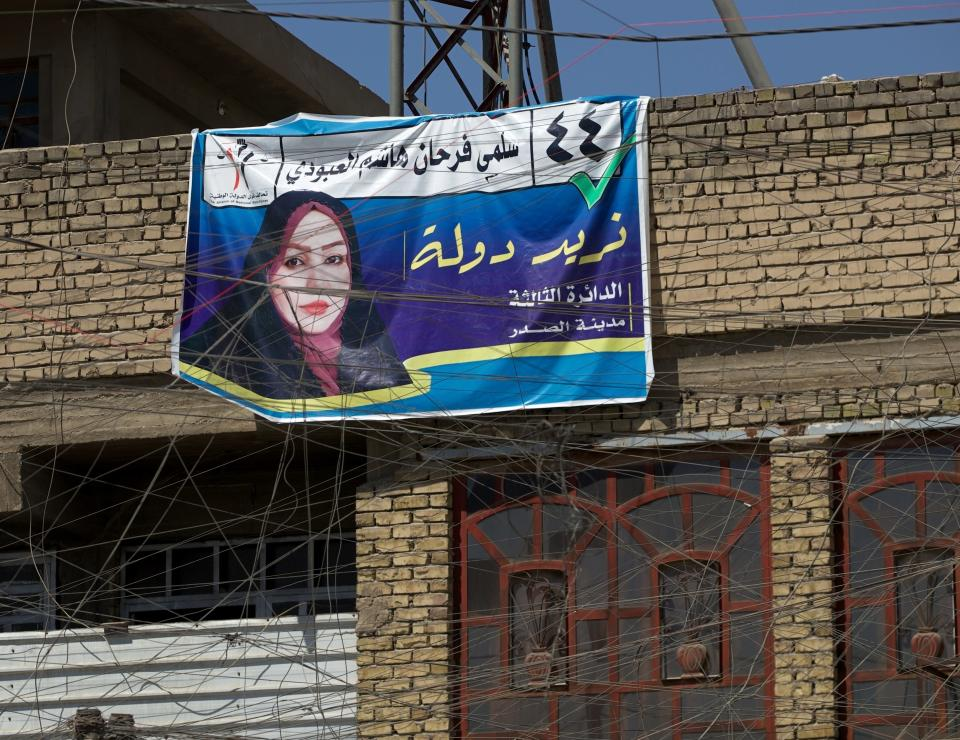 A campaign poster for upcoming early parliamentary elections is hanging behind a private generator network wires in Baghdad, Iraq, Monday, Sept. 20, 2021. In Iraq, electricity is a potent symbol of endemic corruption, rooted in the country's sectarian power-sharing system. It's perpetuated after each election cycle: Once results are tallied, politicians jockey for appointments in a flurry of negotiations based on the number of seats won. (AP Photo/Hadi Mizban)