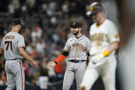 San Francisco Giants third baseman Evan Longoria, center, reacts with relief pitcher Tyler Rogers (71) after the Giants defeated the San Diego Padres 6-5 in a baseball game Tuesday, Sept. 21, 2021, in San Diego. (AP Photo/Gregory Bull)