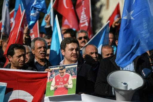 A supporter of China's Muslim Uighur minority holds a placard of Arsenal midfielder Mesut Ozil during a demonstration