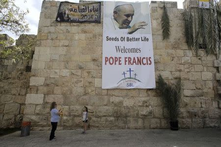 A woman takes a photo of a girl in front of a banner depicting Pope Francis outside Jerusalem's Old City
