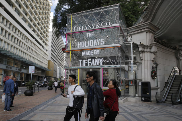In this Thursday, Nov. 29, 2018, photo, Chinese tourists walk past a Tiffany & Co. flagship in Canton Road, the one-stop-shop high street of high-end brands in Hong Kong. The designer boutiques of Manhattan and Paris are feeling the chill of a Chinese economic slowdown that has hammered automakers and other industries. That is jolting brands such as Louis Vuitton and Burberry that increasingly rely on Chinese customers who spend $90 billion a year on jewelry, clothes and other high-end goods. The industry already is facing pressure to keep up as China's big spenders shift to buying more at the spreading networks of luxury outlets in their own country. (AP Photo/Kin Cheung)