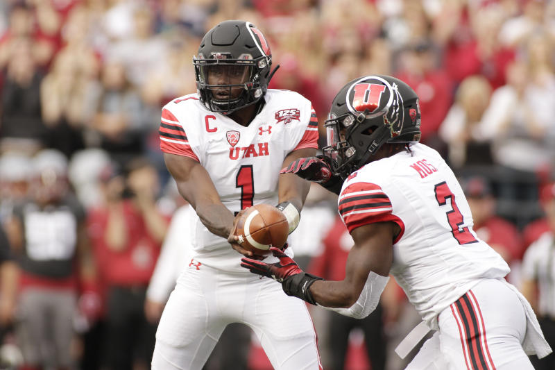 Utah quarterback Tyler Huntley (1) hands the ball to running back Zack Moss (2) during the first half of an NCAA college football game against Washington State in Pullman, Wash., Saturday, Sept. 29, 2018. (AP Photo/Young Kwak)