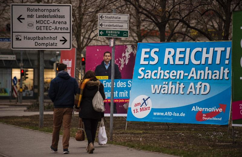 "A couple walks past a campaign poster of the right-wing populist Alternative for Germany party that reads, ""Enough is enough, Saxony-Anhalt votes for AfD"", in Magdeburg, Germany on March 11, 2016 (AFP Photo/John MacDougall)"
