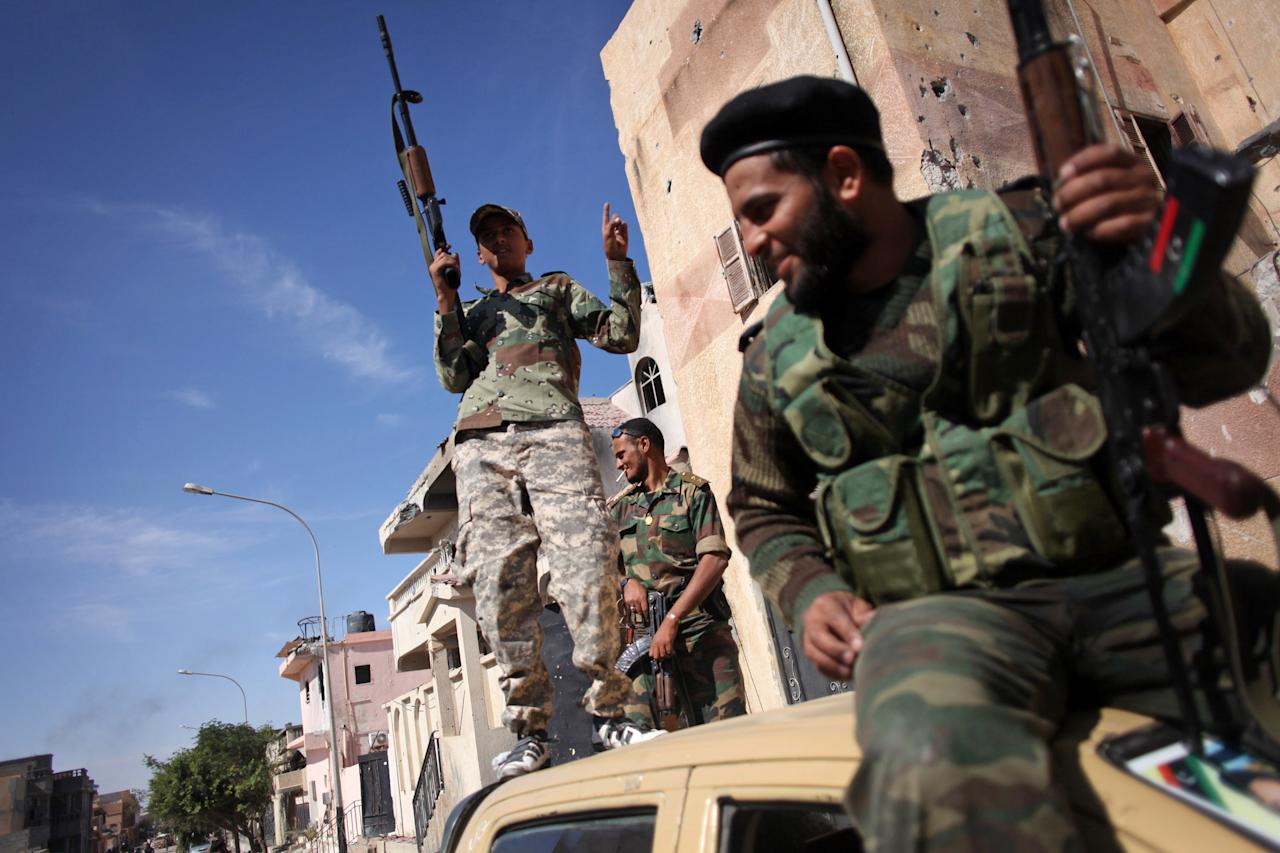 Revolutionary fighters celebrate the capture of Sirte, Libya, Thusday, Oct. 20, 2011. Officials in Libya's transitional government said Moammar Gadhafi was captured and possibly killed Thursday when revolutionary forces overwhelmed his hometown, Sirte, the last major bastion of resistance two months after the regime fell. Amid the fighting, a NATO airstrike blasted a fleeing convoy that fighters said was carrying Gadhafi. (AP Photo/Manu Brabo)