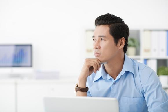 An investor at a computer, deep in thought