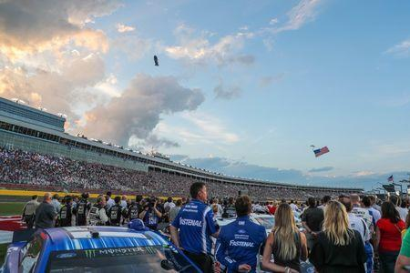 May 19, 2018; Concord, NC, USA; Clouds gather as a parachutist lands with the American flag during the NASCAR Cup Series All-Star Open at Charlotte Motor Speedway. Kevin Harvick goes on to win the All Star Open. Mandatory Credit: Jim Dedmon-USA TODAY Sports