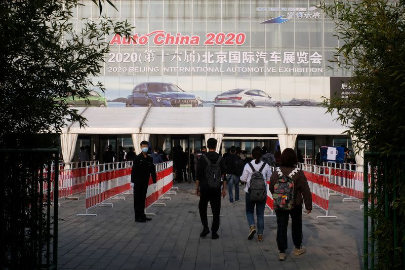 People wearing face masks following the coronavirus disease (COVID-19) outbreak enter the venue of the Beijing International Automotive Exhibition, or Auto China show, in Beijing
