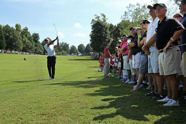 Tiger Woods hits from the edge of the first fairway during the second round of the Tour Championship golf tournament at East Lake Golf Club in Atlanta, Friday, Sept. 20, 2013. .(AP Photo/Atlanta Journal-Constitution, Jason Getz)
