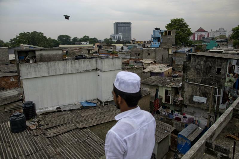 A Muslim volunteer stands in a roof of a mosque to spot possible attackers during Friday prayers in Colombo, Sri Lanka, Friday, April 26, 2019. Religious leaders cancelled large public gatherings amid warnings of more attacks, along with retaliatory sectarian violence in Sri Lanka though some still held communal Friday prayers at mosques. (AP Photo/Gemunu Amarasinghe)