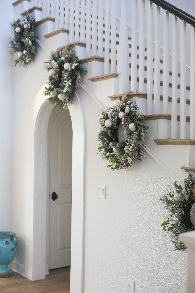 """<p>If you're like Danielle Schaffer of <a href=""""https://citygirlgonemom.com/decorating-for-the-holidays-with-pottery-barn/"""" rel=""""nofollow noopener"""" target=""""_blank"""" data-ylk=""""slk:City Girl Gone Mom"""" class=""""link rapid-noclick-resp"""">City Girl Gone Mom</a>, you'll want a neutral palette on top of a clean, minimal backdrop. Here, she simply hung some wreaths with earthy elements lining the bottom of the steps.</p>"""