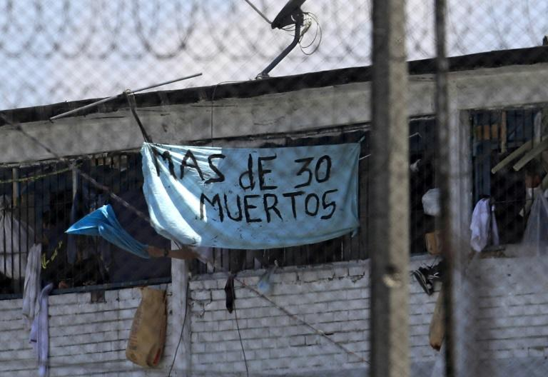 """Inmates at Bogota's La Modelo prison hold up a sign saying, """"More than 30 Dead"""" after a night of rioting in one of Colombia's biggest prisons, on March 22, 2020"""