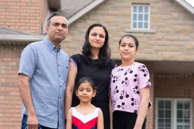 Ankit Patel, 38, with his wife Bhruvei and daughters Jaivy and Haley, have been living at his mother's house for months despite buying their dream home in January because of tenant issues.  (Bobby Hristova/CBC - image credit)
