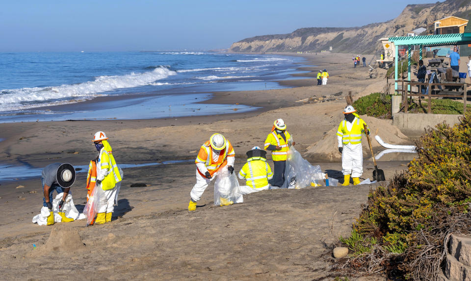 Shoreline cleanup crews pick up tar balls that have washed ashore along the beach at Crystal Cove State Park in Laguna Beach, Calif., Thursday, Oct. 14, 2021. Shoreline cleanup crews continue to pick up tar balls that have washed ashore onto the sand, rocks and vegetation, remnants of the offshore oil spill near Huntington Beach in early October. (Mark Rightmire/The Orange County Register via AP)
