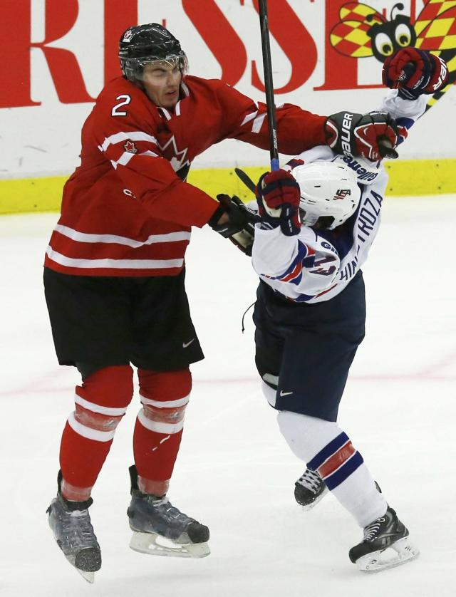 Canada's Adam Pelech (L) checks United States' Vince Hinostroza during the third period of their IIHF World Junior Championship ice hockey game in Malmo, Sweden, December 31, 2013. REUTERS/Alexander Demianchuk (SWEDEN - Tags: SPORT ICE HOCKEY)