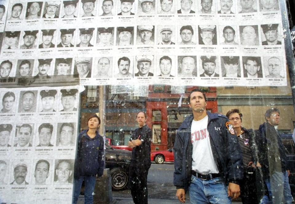 Pedestrians look at photos of missing police and fire personnel missing  a couple of weeks after the attacks (Getty)