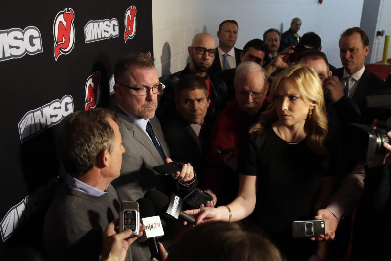 New Jersey Devils interim general Tom Fitzgerald, second from left, looks on as owner Josh Harris, left, speaks to announce Ray Shero was fired prior to an NHL hockey game Sunday, Jan. 12, 2020, in Newark, N.J. (AP Photo/Adam Hunger)
