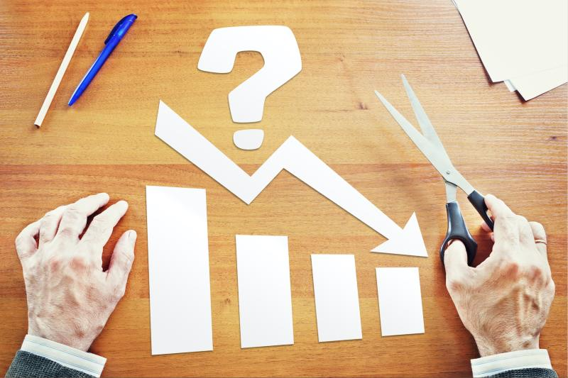 A man holds a pair of scissors in one hand, in front of a paper cutout design of a question mark, bar chart, and declining arrow.