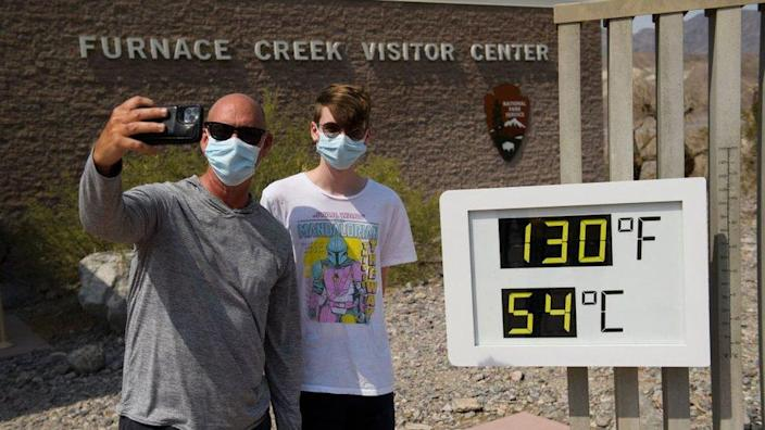 Tourists on a road trip from Texas, take pictures with a thermometer displaying temperatures of 130 Degrees Fahrenheit (54 Degrees Celsius) at the Furnace Creek Visitor's Center at Death Valley National Park