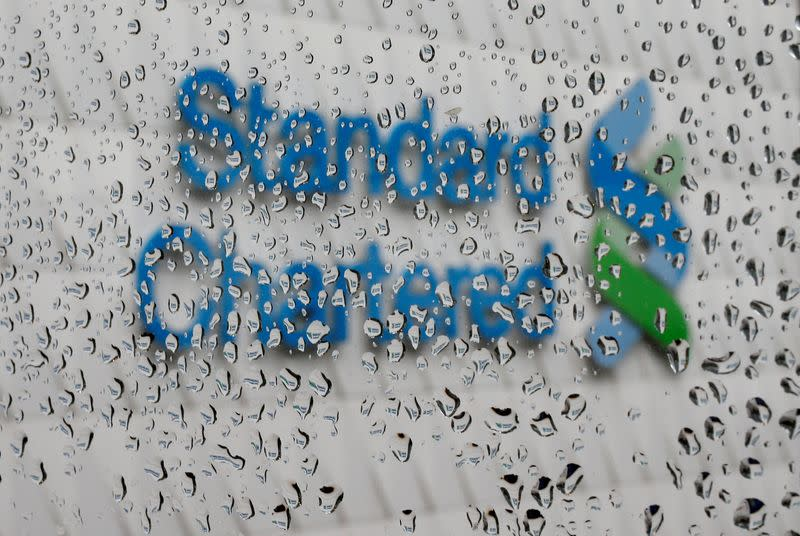FILE PHOTO: A Standard Chartered logo at its headquarters is seen through a window with raindrops, in Hong Kong