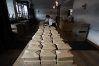 FILE - In this Friday, March 27, 2020 file photo, Nightbird Restaurant pastry chef Hope Waggoner prepares dinner boxes that were delivered to hospital workers in San Francisco. Taxpayers will pay restaurants to make three meals a day for California's millions of seniors during the coronavirus pandemic, Gov. Gavin Newsom announced Friday, April 24, 2020, putting the industry back to work and generating sales tax collections for cash-strapped local governments. California has about 5.7 million people 65 and older, but not all of them will be eligible, and some will have to meet income thresholds. (AP Photo/Jeff Chiu, File)