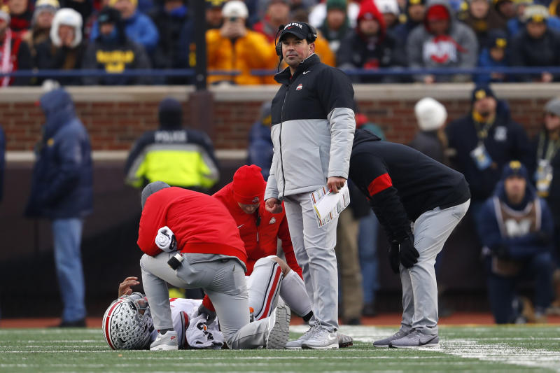 Ohio State head coach Ryan Day looks on as quarterback Justin Fields is helped by medical staff after being injured in the second half of an NCAA college football game against Michigan in Ann Arbor, Mich., Saturday, Nov. 30, 2019. Fields returned to the game with a knee brace. (AP Photo/Paul Sancya)
