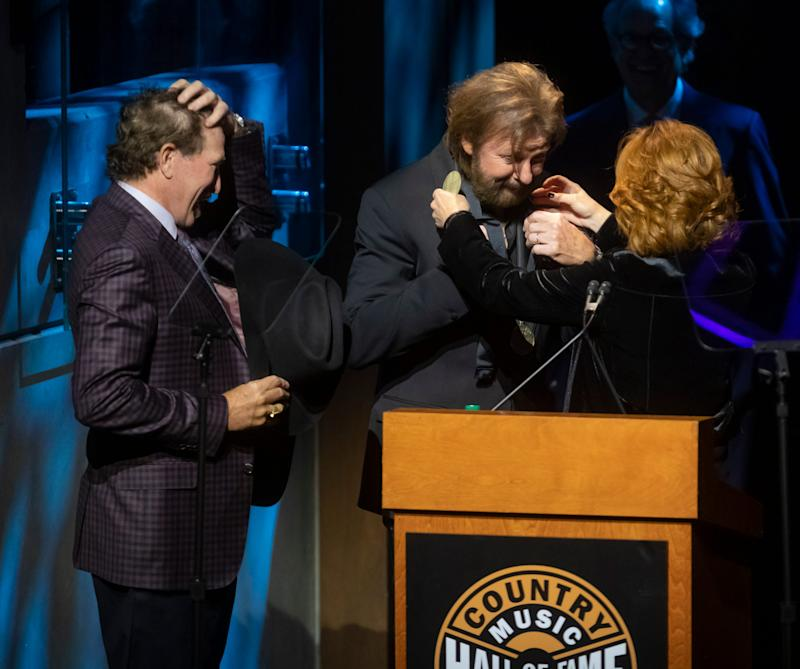 Reba McEntire presents Brooks & Dunn with their medallions during the Medallion Ceremony at the Country Music Hall of Fame Sunday, October 20, 2019.