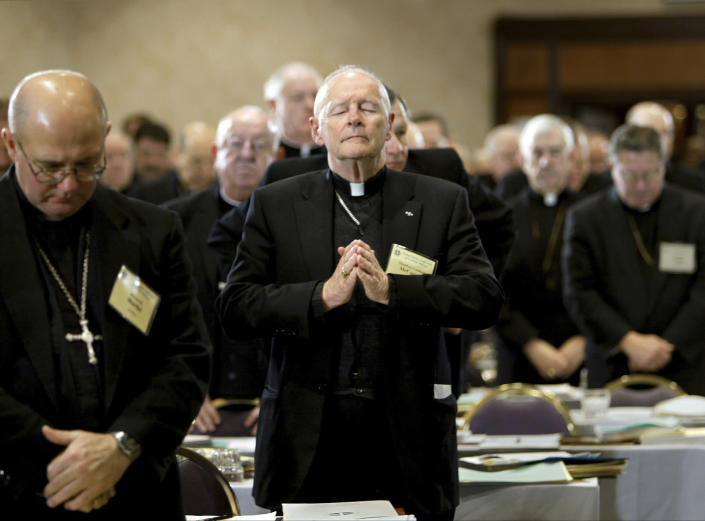 FILE - In this Nov. 10, 2003 file photo, Cardinal Theodore Edgar McCarrick, Archbishop of Washington, D.C., center, joins his fellow clergy in prayer at the end of the opening session of the U.S. Conference of Catholic Bishops meeting in Washington. On Tuesday, Nov. 10, 2020, the Vatican is taking the extraordinary step of publishing its two-year investigation into the disgraced ex-Cardinal McCarrick, who was defrocked in 2019 after the Vatican determined that years of rumors that he was a sexual predator were true. (AP Photo/J. Scott Applewhite, File)