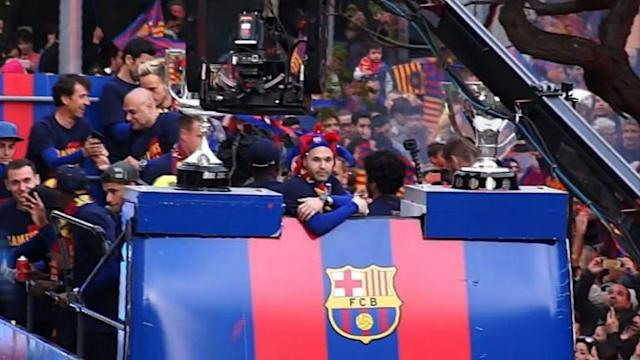 Ecstatic Barcelona fans greet Lionel Messi and other players as they parade the La Liga and Copa del Rey trophies through the streets of the city.