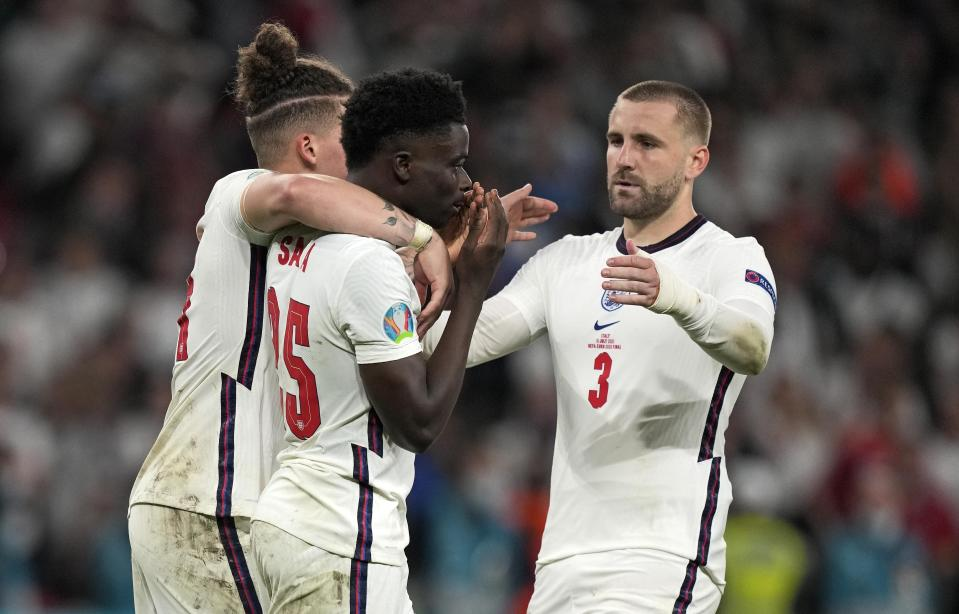 England's Bukayo Saka, center, is comforted after he missed to score the last penalty during the penalty shootout of the Euro 2020 soccer championship final between England and Italy at Wembley stadium in London, Sunday, July 11, 2021. (AP Photo/Frank Augstein, Pool, File)