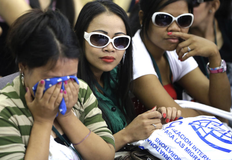 Overseas Filipino Workers, who fled the civil war in Syria, react upon arriving at the Ninoy Aquino International Airport via a chartered flight by the International Organization for Migration on Tuesday, Sept. 11, 2012, in Manila, Philippines. The nearly 300 workers, all of them young women who worked as babysitters and maids in Syria, said they were scared for their safety and sought shelter at the Philippine Embassy in Damascus until their repatriation Tuesday. (AP Photo/Bullit Marquez)